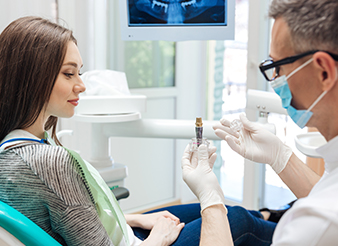 Dentist and patient looking at dental implant model