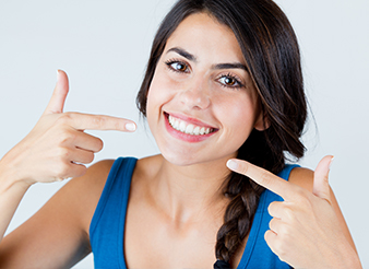 Woman pointing to flawless smile