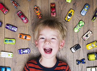 Laughing young boy surrounded by toy cars