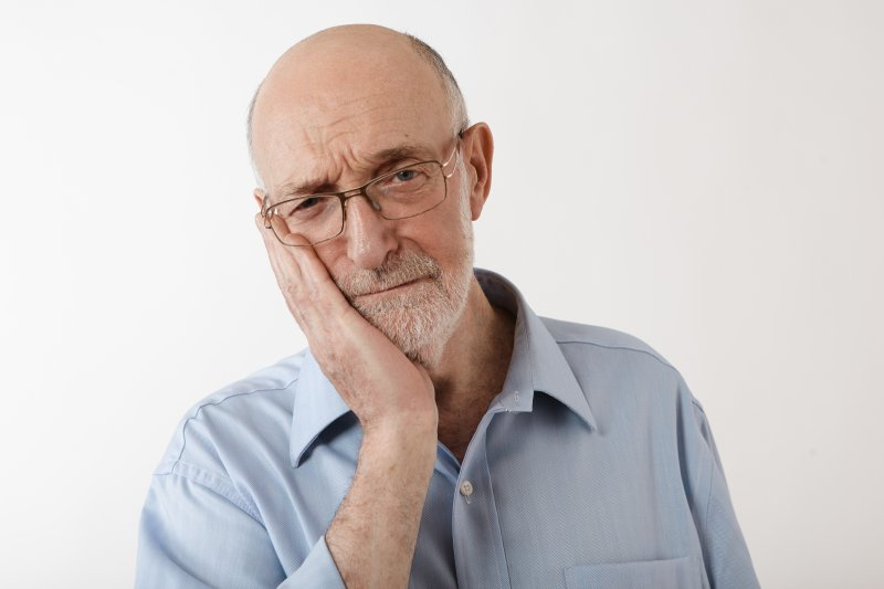 older man in pain from failed dental implants in Lewisville